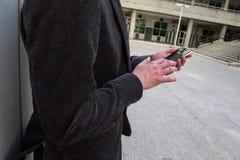 Der Geschäftsmann, der von der Arbeit und von ihm stillsteht, spricht mit seinem Smartphone stockfotos