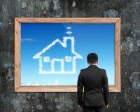 Der Geschäftsmann, der weiße Hausform des Holzrahmens betrachtet, bewölkt sich Stockbilder