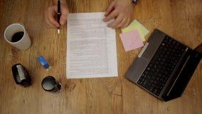 Der Geschäftsmann, der zu Hause Schreibtisch bearbeiten und einen Vertrag überprüfen, das Zeichen und der Stempel schließen, Drau stock footage