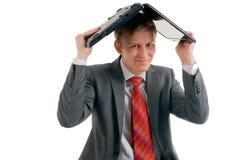 Der Geschäftsmann hat den Laptop auf einem Kopf gekleidet lizenzfreie stockfotos