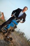 Der Geschäftsmann hinter einem Traktor. Lizenzfreie Stockfotografie