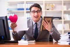 Der Geschäftsmann im Heiligvalentinsgrußkonzept im Büro Stockbilder