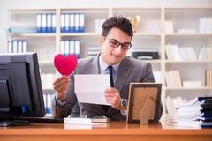 Der Geschäftsmann im Heiligvalentinsgrußkonzept im Büro Lizenzfreies Stockbild