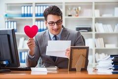 Der Geschäftsmann im Heiligvalentinsgrußkonzept im Büro Lizenzfreies Stockfoto