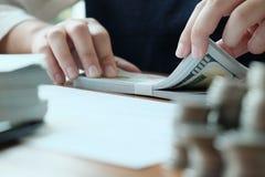 Der Geschäftsmann, der Investitionsdiagramme analysiert und Taschenrechner bedrängt, knöpft über Dokumenten lizenzfreie stockfotografie