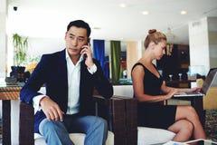 Der Geschäftsmann mit ernstem Gesicht Arbeit besprechend gibt durch Handy, die junge intelligente Frau heraus, die an Laptop-Comp Stockbilder