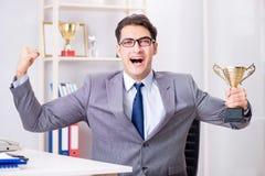 Der Geschäftsmann mit prize Schale für Leistungen im Büro Stockfotos