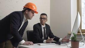 Der Geschäftsmann mit zwei Jungen, Architekt, besprechen das Projekt und betrachten den Monitor im Büro Erbauer, Ingenieure, Konz stock video