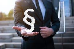 Der Geschäftsmann, der Paragraphen hält, unterzeichnen herein seine Hand Lizenzfreies Stockbild