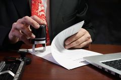 Der Geschäftsmann setzt einen Stempel auf den Vertrag Stockfotos