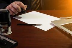 Der Geschäftsmann setzt einen Stempel auf den Vertrag Lizenzfreie Stockfotos