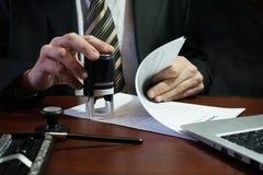 Der Geschäftsmann setzt einen Stempel auf den Vertrag Stockbild