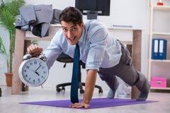 Der Geschäftsmann, der Sport im Büro während des Bruches tut Lizenzfreies Stockfoto