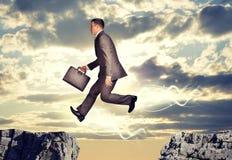 Der Geschäftsmann springend über Abgrund Lizenzfreies Stockfoto