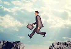 Der Geschäftsmann springend über Abgrund Lizenzfreie Stockbilder
