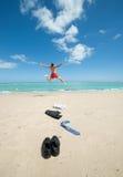 Der Geschäftsmann springend auf den Strand Stockfotos