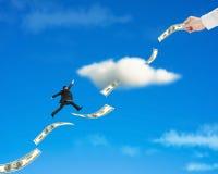 Der Geschäftsmann springend auf Geldtendenz durch Wolke mit Hand-holdi Stockfotos