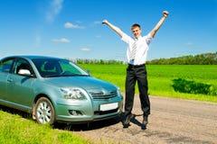 Der Geschäftsmann springend nahe Auto Stockfotografie