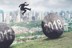 Der Geschäftsmann springend zwischen Zahlen 2017 und 2018 Lizenzfreie Stockfotos