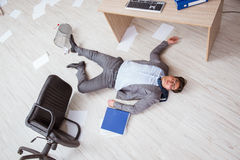 Der Geschäftsmann tot auf dem Büroboden lizenzfreie stockbilder