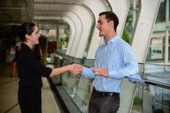 Der Geschäftsmann und Geschäftsfrau, die Hände für Erfolgsvereinbarung rütteln und sprechen über Geschäft Stockbilder