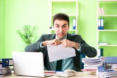 Der Geschäftsmann verärgert mit der übermäßigen Arbeit, die im Büro sitzt stockbild