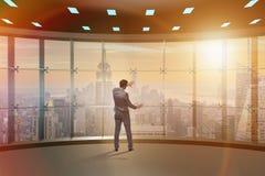 Der Geschäftsmann vor Bürofenster denkend an neue Herausforderungen stockfotografie