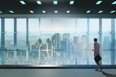 Der Geschäftsmann vor Bürofenster denkend an neue Herausforderungen stockfoto