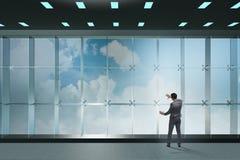 Der Geschäftsmann vor Bürofenster denkend an neue Herausforderungen Lizenzfreie Stockfotos