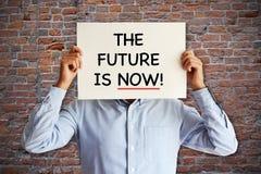 """Der Geschäftsmann, der whiteboard mit """"the Zukunft hält, ist now† Text, brauner Ziegelsteinhintergrund Lizenzfreie Stockfotografie"""