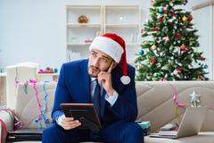 Der Geschäftsmann, der zu Hause während des Weihnachten arbeitet Lizenzfreies Stockbild