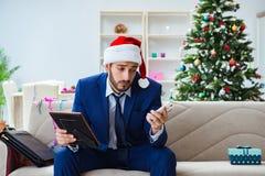 Der Geschäftsmann, der zu Hause während des Weihnachten arbeitet Lizenzfreies Stockfoto