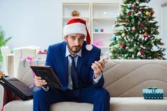 Der Geschäftsmann, der zu Hause während des Weihnachten arbeitet Stockfoto