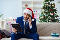 Der Geschäftsmann, der zu Hause während des Weihnachten arbeitet Lizenzfreie Stockfotos