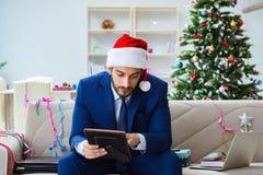Der Geschäftsmann, der zu Hause während des Weihnachten arbeitet Stockfotografie