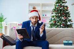 Der Geschäftsmann, der zu Hause während des Weihnachten arbeitet Stockbilder
