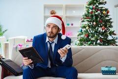 Der Geschäftsmann, der zu Hause während des Weihnachten arbeitet Lizenzfreie Stockbilder