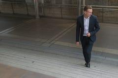 Der Geschäftsmannabnutzungsschwarzanzug, der geht, Treppe in der modernen Stadt, Geschäft steigernd heran, wachsen und Erfolgskon lizenzfreie stockfotografie