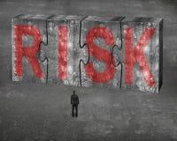Der Geschäftsmann, der rotes Risikowort auf enormem Beton gegenüberstellt, verwirrt connec Lizenzfreies Stockbild