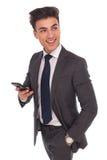 Der Geschäftsmann, der sein Telefon für das Simsen verwendet, schaut, um mit Seiten zu versehen Lizenzfreie Stockfotos
