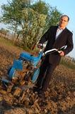Der Geschäftsmann hinter einem Traktor. Stockfoto