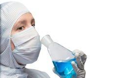 Der Gesundheitsfürsorger hält eine Flasche mit blauer Flüssigkeit und riecht seinen Geruch lizenzfreies stockfoto