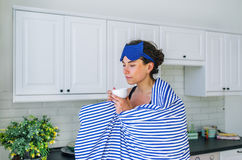 Der Getränktee des jungen Mädchens, der an der modernen Küche steht, Frau schloss Augentraum Lizenzfreie Stockbilder