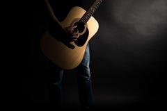 Der Gitarrist in den Jeans spielt eine Akustikgitarre, auf der linken Seite des Rahmens, auf einem schwarzen Hintergrund Horizont Lizenzfreies Stockbild