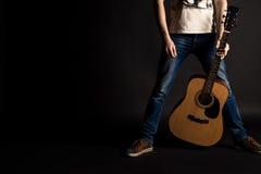 Der Gitarrist, der seine linke Hand mit einer Akustikgitarre auf einem Schwarzen hält, lokalisierte Hintergrund Lizenzfreie Stockbilder