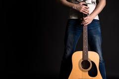 Der Gitarrist, der zwei Hände mit einer Akustikgitarre auf einem Schwarzen hält, lokalisierte Hintergrund Lizenzfreie Stockfotografie