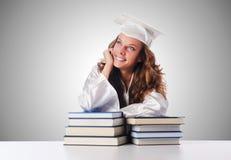 Der glückliche Absolvent mit vielen Büchern auf Weiß stockfotos