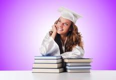 Der glückliche Absolvent mit vielen Büchern auf Weiß stockbilder