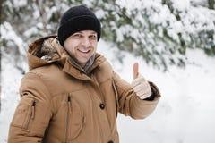 Der glückliche aktive Mann, der sich Daumen zeigt, alles ist OKAY und gut Schneemann gebildet vom weißen tropischen Sand auf exot Stockbilder