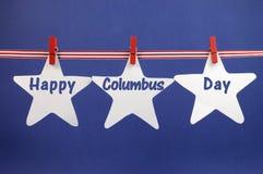 Der glückliche Columbus Day-Mitteilungsgruß, der über weißen Stern geschrieben wird, kardiert das Hängen vom Rotstreifenband und - Stockfotografie